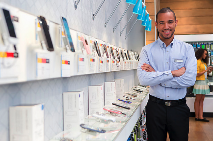 Man Standing Next to Wall of Cellphones