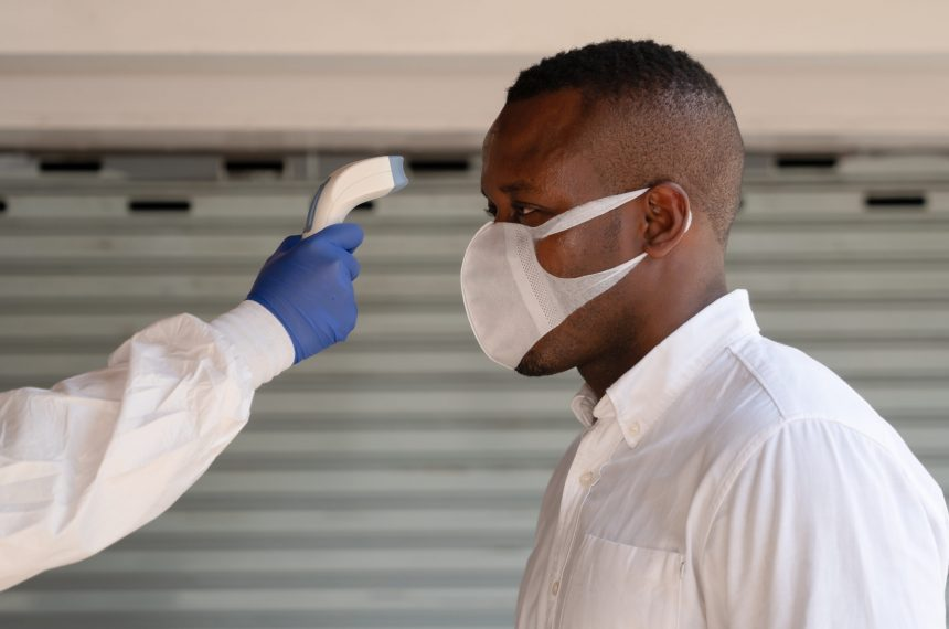 health control staff in virus protection clothing and face shield scanning temperature with digital device to african american businessman to check for fever in coronavirus covid-19 spreading prevention
