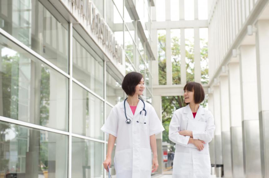Two Doctors Walking Through Window-Filled Building Hallway
