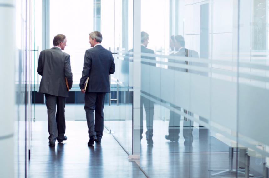 Two Businessmen Walking Down Office Building Hallway