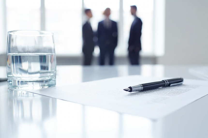 Close-up View of Paper, Pen and Glass of Water with Businessmen in Background