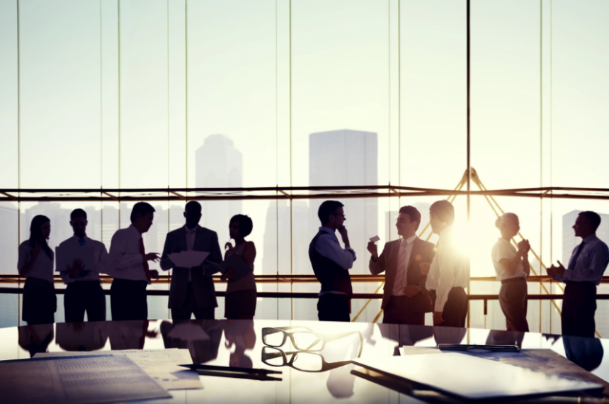 Group of Business People Talking in Office with Tall Windows