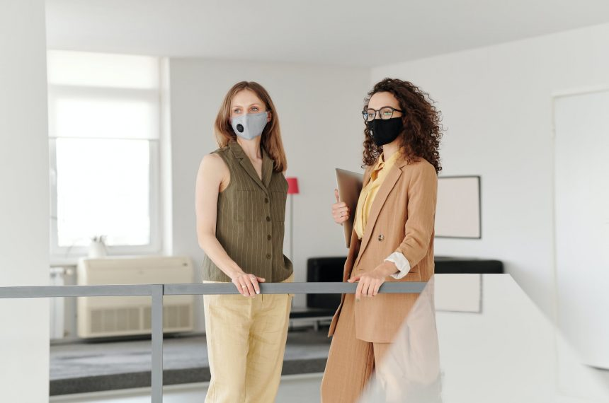 two women in masks checking in at front desk